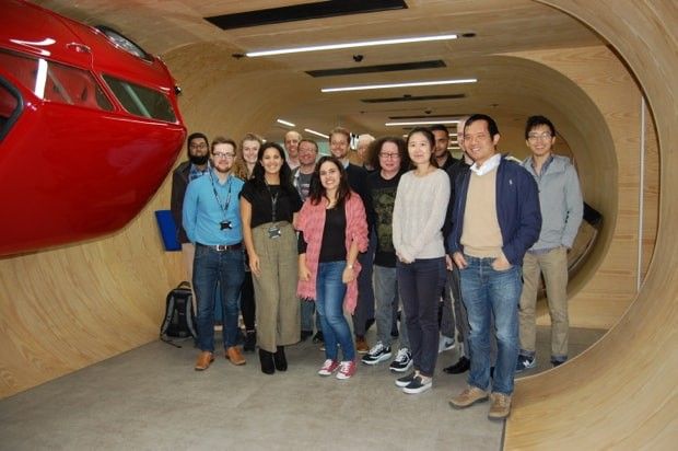 Photo of group in Autotrader's reception, with a Mini half way up the wall