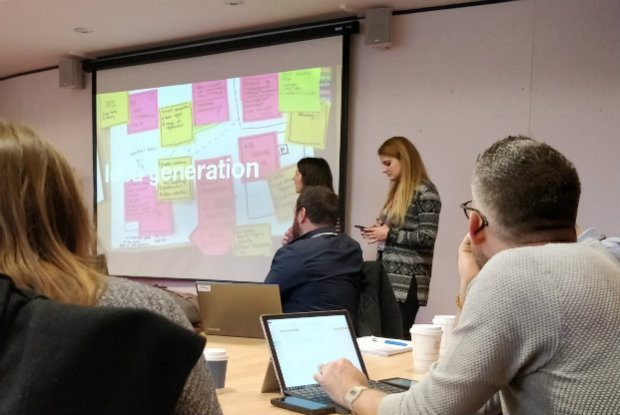 A meeting room showing 5 members of the community looking at a slide saying 'Idea generation'.