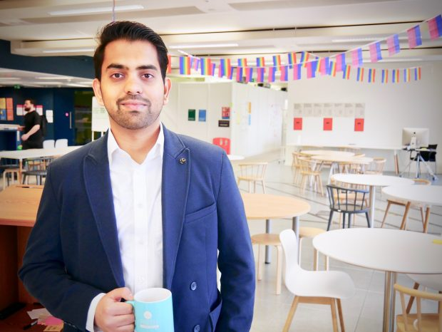 Bharath Vadhoola at the Government Digital Service offices holding a blue mug