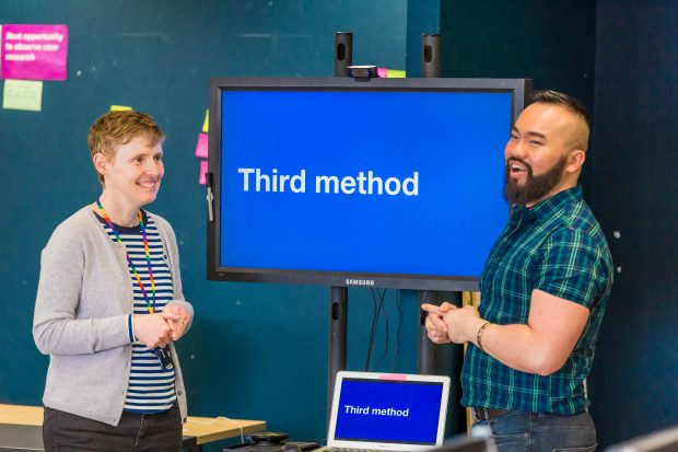 Louise and Haur stand either side of a TV screen, about to present to team colleagues about the 'Third method'
