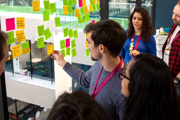 Data scientists reviewing a set of post-it notes on a glass wall