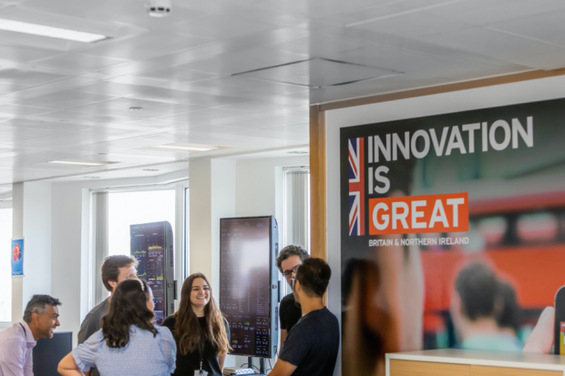 People having an informal stand-up meeting, next to a large 'Innovation is Great' poster
