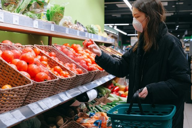Woman wearing a facemask, shopping for tomatoes in a supermarket
