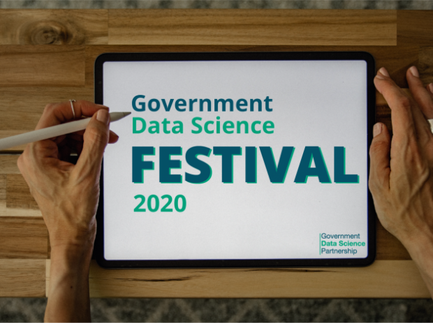 A person holding a tablet computer displaying the Government Data Science Festival logo
