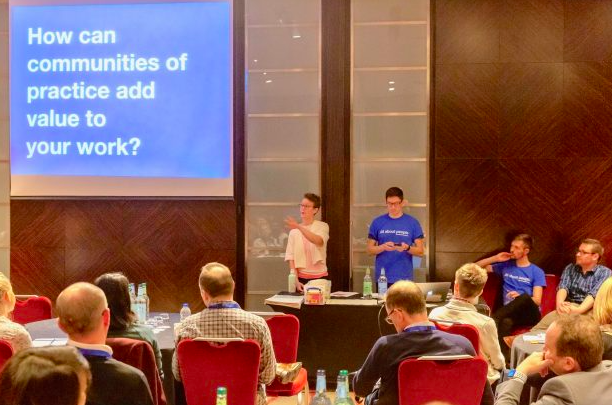 Image of two people presenting at a conference, in front of a screen showing 'How can communities of practice add value to your work'