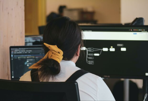 Women at a desk working with two computer screens.